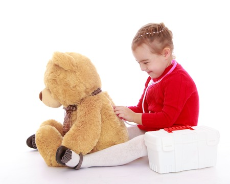 playing with spoon: Funny little girl in a red dress sitting on the floor and plays with a big Teddy bear in the hospital. The girl applied to the back of the bear phonendoscope . She listens to his breathing - Isolated on white background Stock Photo