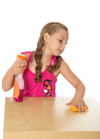 industrious: Industrious girl of school age is cleaning up in the kitchen. Girl rubbing the table with a Sponge with detergent - Isolated on white background
