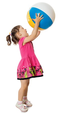 Cheerful little girl in a short pink dress playing with a large inflatable ball. The girl raised the ball with his hands in the top - Isolated on white background Фото со стока
