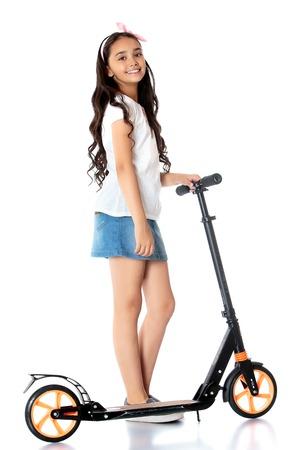 scooter: hermosa chica de aspecto oriental con el pelo largo oscuro y rizado en una corta mini falda vaquera monta un scooter - Aislado en el fondo blanco