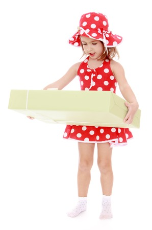 giftwrapped: Beautiful little girl in short summer red polka dot dress and matching hat. The girl grabbed the large gift-wrapped box with a gift -Isolated on white background