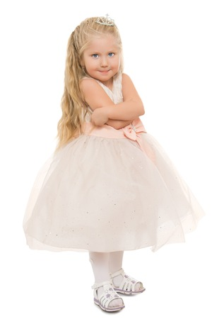 Adorable little round-faced girl with long blonde flowing hair, dressed in a white dress folded her arms -Isolated on white background Stock Photo