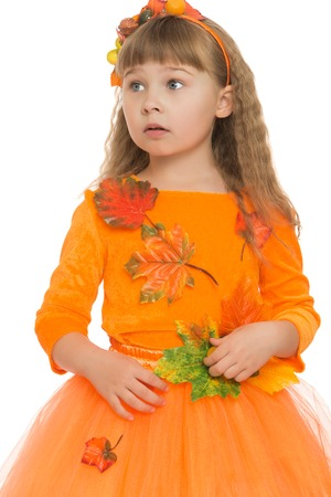bangs: Sweet, beautiful little girl with flowing blonde hair and short bangs , elegant, orange dress. The girl thoughtfully looks aside. Closeup -Isolated on white background