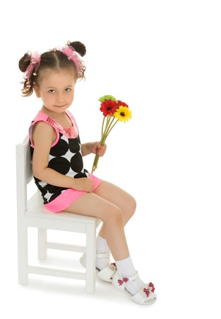 shy girl: Cute little shy girl in fashionable short dress sitting on a chair . Girl holding a bouquet of colorful flowers - Isolated on white background Stock Photo