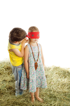 hayloft: Little boy girl Tying with a scarf eyes. Children play in the hayloft hide-and-seek -Isolated on white background