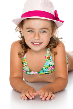 tanned girl: Joyful little tanned girl in swimsuit and hat laying on the floor and looking at the camera - Isolated on white background.The concept of a Happy childhood and child development Stock Photo