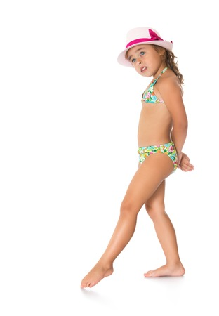 petite girl: Shy, petite, tanned girl in a bathing suit and hat thoughtfully draws his foot on the floor - Isolated on white background.The concept of a Happy childhood and rest Stock Photo