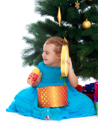 fancy box: Very cute little girl in fancy blue dress sitting on the floor near the Christmas tree. Kneeling girl holding a round box from which she gets gifts - Isolated on white background.The concept of childhood and the holidays Stock Photo