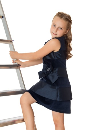 working dress: Stylish long-haired girl of school age,in a beautiful dark blue dress. The girl put her foot on the stairs . Closeup-Isolated on white background.The concept of a Happy childhood and child development Stock Photo