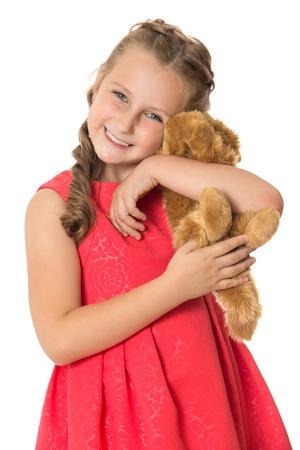 oso blanco: Niña elegante en un vestido rojo brillante abraza suavemente el oso de peluche. Primer - aislada sobre fondo blanco Foto de archivo