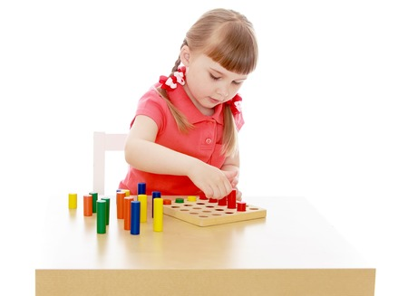 montessori: Keen little girl sitting at the table doesnt work with Montessori material - Isolated on white background
