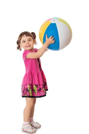 gooit gelukkig meisje in een korte roze jurk een grote gestreepte bal - die op een witte achtergrond