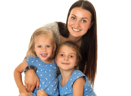 long silky hair: The concept of the celebration and the value of family relationships.Very beautiful young mother with long silky hair,tenderly embracing his beloved daughters. Little girls of different ages in identical blue dresses with polka dots. Closeup - Isolated on