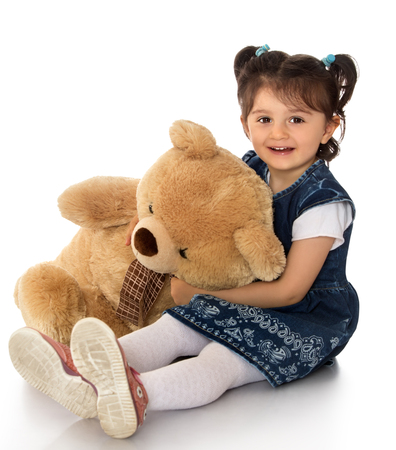 kids toys: Happy little dark-haired girl in a blue dress and white pantyhose plays with a Teddy bear - Isolated on white background