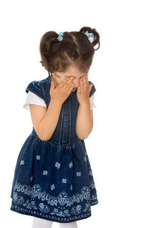 beautiful crying woman: Upset little dark-haired girl in a blue dress and white stockings is crying hiding her face. Closeup - Isolated on white background Stock Photo
