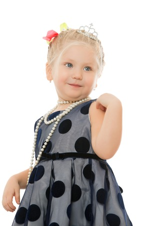 chubby girl: Fashionable very small chubby girl, nice gray dress with polka dots. Neck girls long string of pearls. Closeup - Isolated on white background Stock Photo