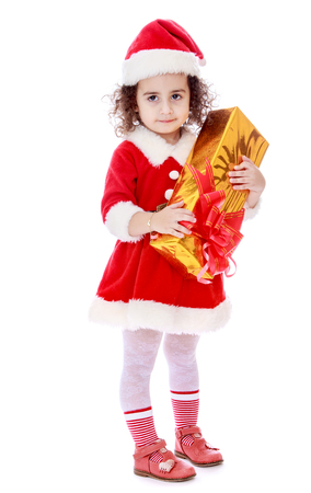 children clothing: Very cute little curly girl in a suit and cap of Santa Claus waiting for the Christmas holidays. In the hands of the girls beautifully packaged with a gift box - Isolated on white background