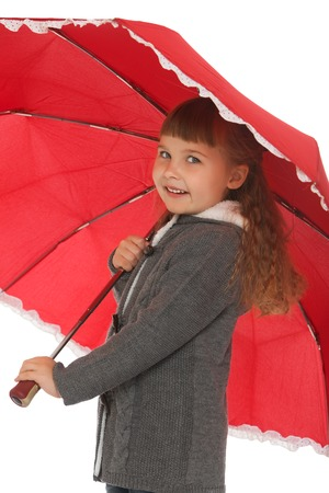 umbrela: Cute little girl with flowing dark hair and short bangs, covers his head with a big red umbrella . Closeup - Isolated on white background Stock Photo