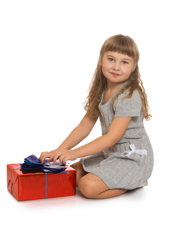beautiful bangs: Beautiful Caucasian little girl with long blonde, flowing hair and short bangs, in a gray knitted dress with short sleeves. A girl sits on your lap and unpacks the box, which she gave to my parents for my birthday - Isolated on white background Stock Photo