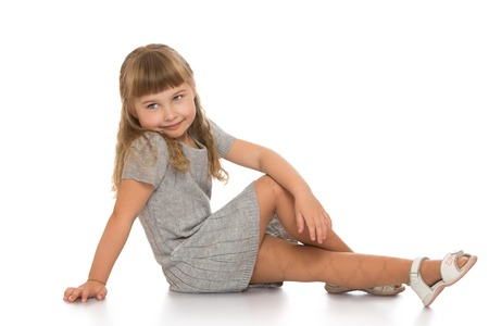 little colours: Beautiful Caucasian little girl with long blonde, flowing hair and short bangs, in a gray knitted dress with short sleeves. Girl sitting on the floor turning the camera sideways - Isolated on white background