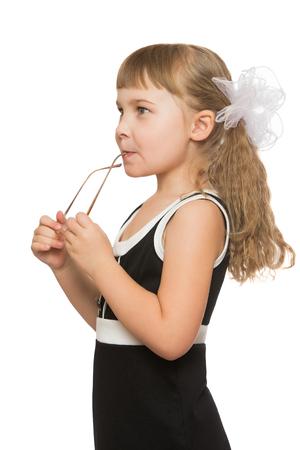 petite fille avec robe: Belle petite fille aux longs, blond, cheveux luxuriante, qui est tress� grands arcs blancs, en noir robe courte. La fille tient des lunettes. Gros plan - isol� sur fond blanc Banque d'images