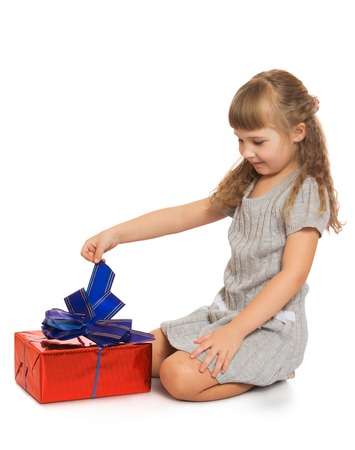 tied down: Curious, little, blond girl in grey short dress sat down beside red box, tied with a blue bow. Girl wants to untie the bow . It is Interesting that there is - Isolated on white background.The concept of a Happy childhood and child development