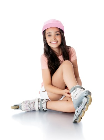 Beautiful girl Oriental appearance, with long dark hair sitting on the floor and puts his feet on roller skates. Girl wearing pink shirt and short white shorts - Isolated on white background.The concept of a Happy childhood and sport