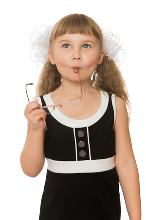 little girl dress: Smart little girl with long bushy tails, white bows and short bangs on the head thoughtfully holding points. Stock Photo