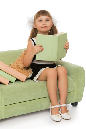 young: Smart , thoughtful little girl with long bushy tails, white bows and short bangs on her head sitting on the couch. The girl hugs the book which reads.  -Isolated on white background.The concept of a Happy childhood and education Stock Photo