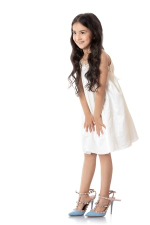 Elegant, slim little girl of Eastern appearance, with long dark hair, trying on mom's high-heeled shoes. Shoes on the feet of the girls are very large - Isolated on white background