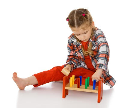 montessori: Keen little girl in Montessori kindergarten playing with toys - Isolated on white background.The concept of a Happy childhood and education