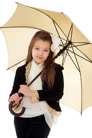 umbrela: Stylish round-faced teenage girl in a black pantsuit. The girl is holding on his shoulder a large yellow umbrella . closeup - Isolated on white background