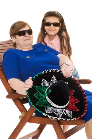 grandkids: Old grandma along with his beloved granddaughter sunbathing on the lounger. Grandmother is holding a big Mexican hat , sombrero. The eyes of the grandmother and her granddaughter dark sunglasses - Isolated on white background.The concept of family and Hap