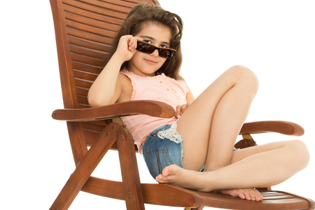 little girl dress: Happy school aged girl sunbathes on the sunbed . in front of girls black sunglasses - Isolated on white background.The concept of a Happy childhood and child development