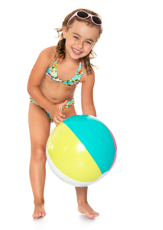 Beautiful, petite, tanned girl in a swimsuit playing on the beach with a big ball - Isolated on white background