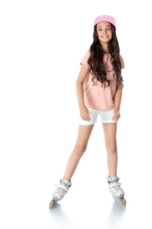 Beautiful,slender, long-haired girl childrens roller-skates. Girl wearing pink top and short white shorts - Isolated on white background Stock Photo