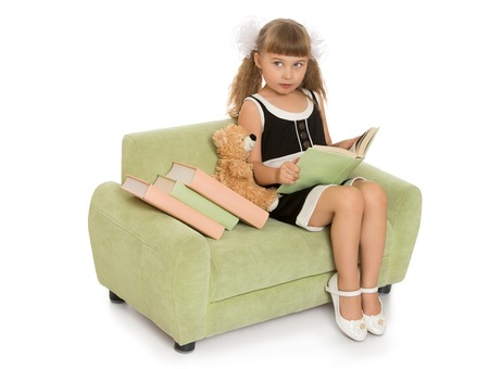 sleeveless dress: Adorable little girl with long , blonde hair that is braided large white bows in elegant black sleeveless dress. Girl sitting on the couch and reading a book -Isolated on white background Stock Photo
