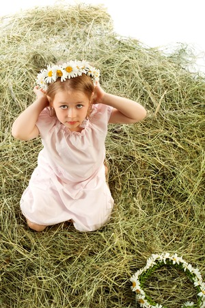 field of daisies: Cute little girl plays in the village on the haystack. She tries on a head a wreath of field daisies . Top view - Isolated on white background Stock Photo