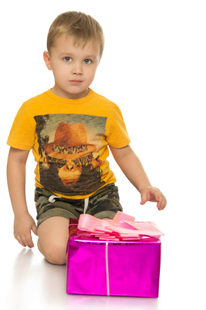 beautifully wrapped: small blond boy in a yellow t-shirt with design on chest, sitting on his knees at the beautifully Packed box in which the wrapped gift - Isolated on white background