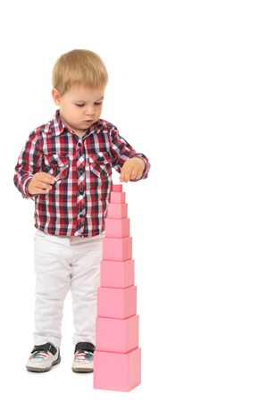 montessori: Enthusiastic little boy builds a pink pyramid , in Montessori kindergarten - Isolated on white background