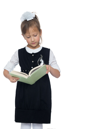 schoolgirl uniform: Cute little schoolgirl in a strict school uniform of black color with enthusiasm reads the book. Closeup - Isolated on white background Stock Photo