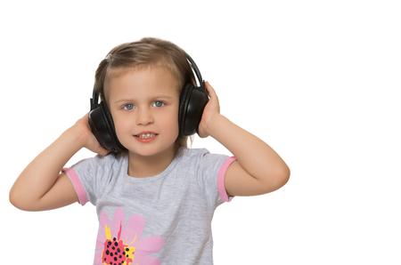 caras felices: Musical niña escucha música en los auriculares estéreo de alta. Primer - Aislado en el fondo blanco Foto de archivo