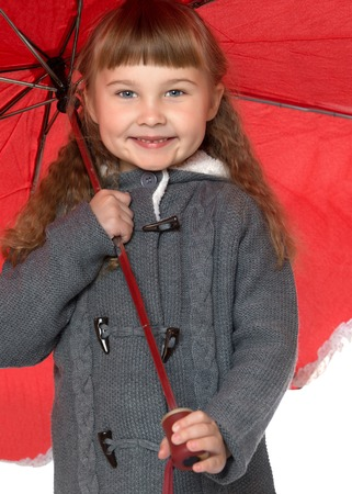 umbrela: Beautiful little girl with short bangs and curly hair hid under a big red umbrella. Closeup - Isolated on white background