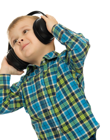funny love: Cheerful little boy listens to music through large headphones black. Closeup - Isolated on white background