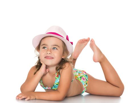 Schattig klein meisje in een roze hoed en een badpak op de grond liggen en kijkt - die op een witte achtergrond