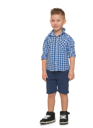 Beautiful little blond boy with a fashionable haircut, blue shorts and blue plaid shirt - Isolated on white background