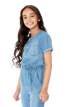 schoolgirl uniform: Stylish girl with long dark hair in denim overalls. Closeup - Isolated on white background