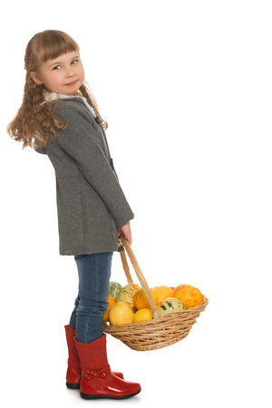 beautiful bangs: Beautiful little girl with blond hair and short bangs, in autumn clothes and red boots. A girl holding a basket in which is autumn harvest - Isolated on white background