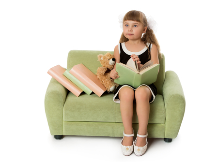 green couch: Pretty little blonde girl with groomed long hair and short bangs,reading a book sitting on a green couch - Isolated on white background Stock Photo