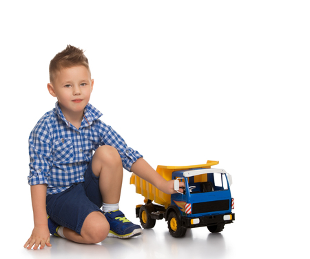 boy shorts: Fashion little boy in blue plaid shirt and shorts is sitting on the couch - Isolated on white background